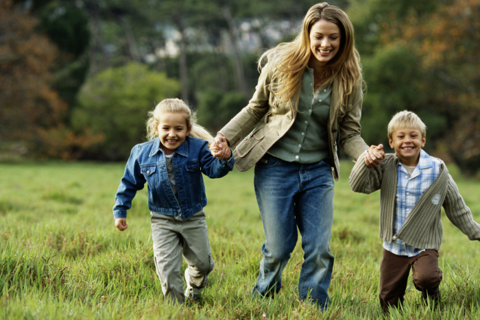 Mother walking with son and daughter (children 4-6) in field, smiling